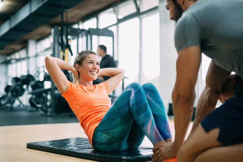 Woman doing situps with personal trainer